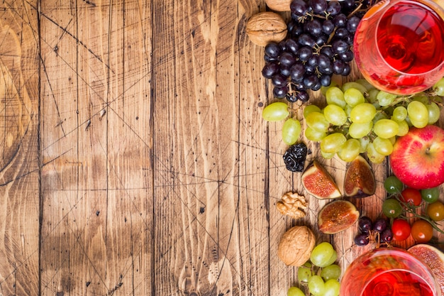 Cheese, wine, baguette grapes figs honey and snacks on the rustic wooden table top with copy space.