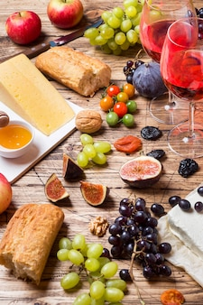 Cheese, wine, baguette grapes figs honey and snacks on the rustic wooden table top.