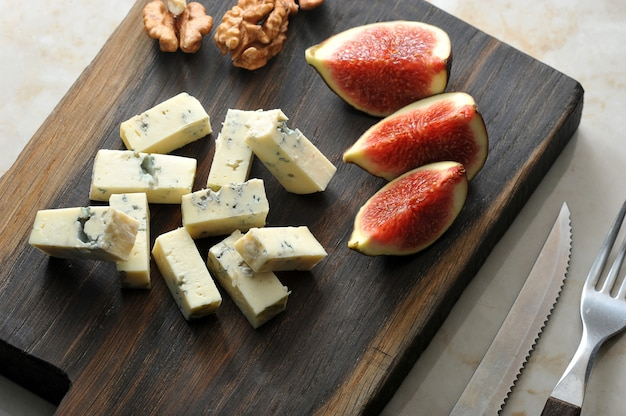 Cheese with blue mold  dorblu, a few slices of figs and walnuts are served on a wooden board. there are cutlery nearby.