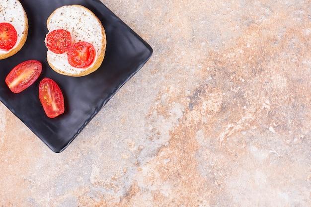 Formaggio con pane e pomodori su un piatto da portata, sullo sfondo di marmo.