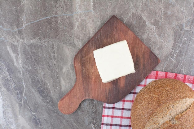 Cheese with brown bread on wooden board. high quality photo