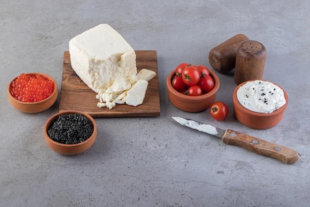 Сыр с икрой и красными свежими помидорами черри на каменном столе.