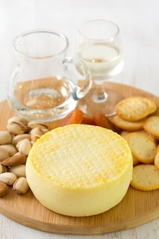 Cheese with cookies, nuts and wine on tray on white