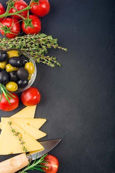 Cheese with fresh herbs, black and green olives, cherry tomatoes, selective focus