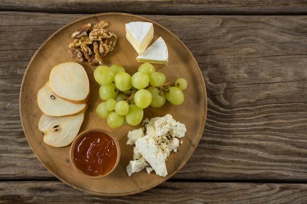 Сыр с виноградом, кусочками яблок, грецкими орехами и соусом на деревянной тарелке