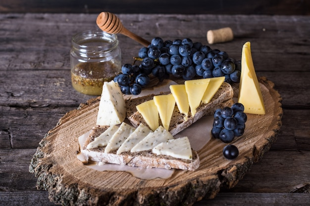 Cheese with grapes, bread, honey. goat cheese with herbs.natural wooden board. bruschetta.