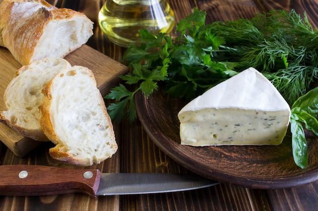 Сыр с зеленью и багетом на деревянных фоне