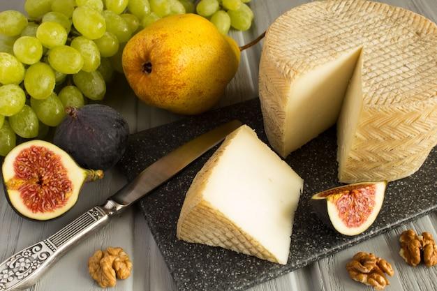 灰色のまな板にナッツとフルーツのチーズ