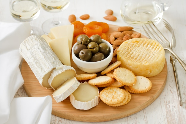 Cheese with olives, dry fruits, cookies and white wine