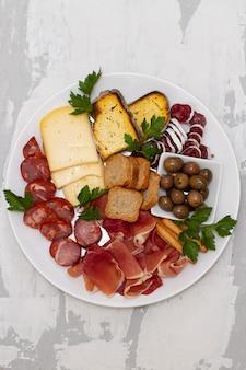 Сыр с прошутто и копчеными колбасками на белом блюде