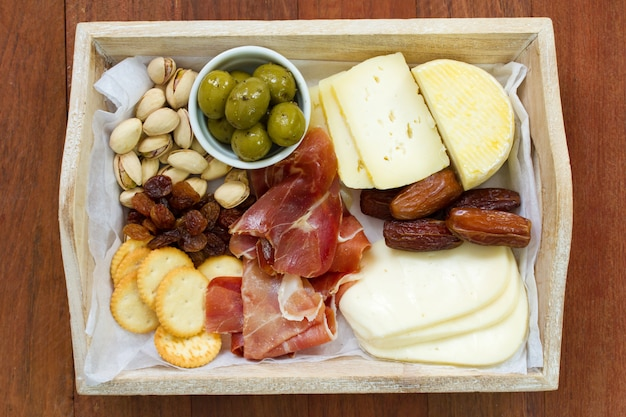 Cheese with prosciutto, cookies, olives