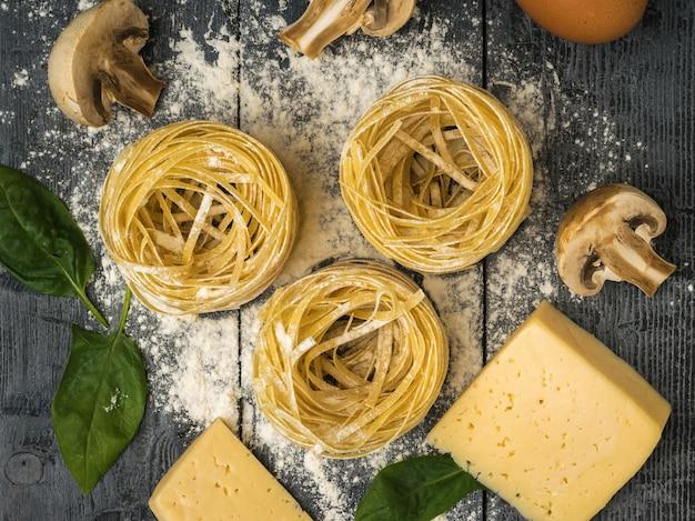 Сыр с закатанными макаронами и грибами на деревянном столе. ингредиенты для приготовления макаронных изделий.
