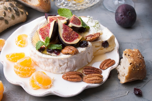 Cheese with white mold and figs, honey and nuts. autumn sweets and fruits and wine. delicious food for dinner. top view.