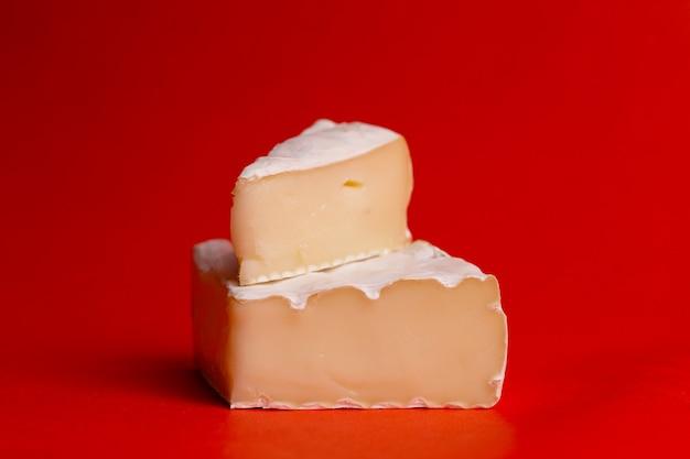 Сыр с белой плесенью на красном фоне крупным планом