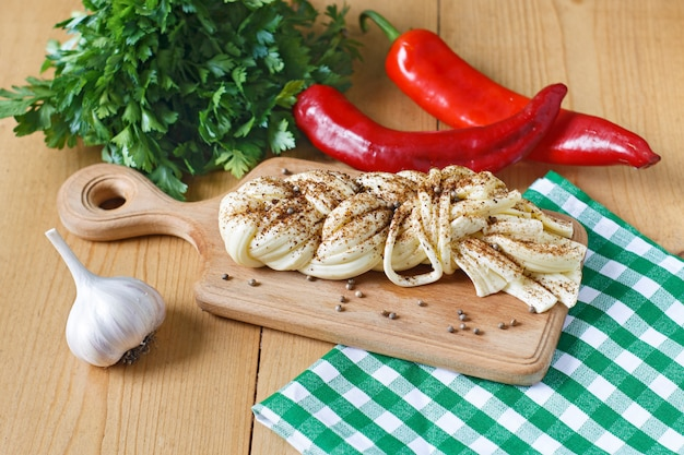 Cheese on wooden board, spices, greens, chili, garlic on a wooden background. sulguni cheese
