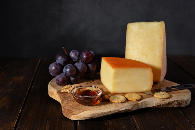 Cheese on a wooden board with nuts and honey