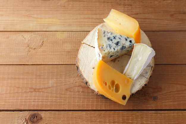 Cheese on wooden boards. camembert, hard yellow cheese, dorblu on wooden stand. top view