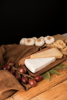 Cheese on wooden tray with grapes and garlic bulbs over table