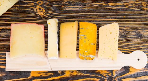 Сырная доска с ассорти из сыров, расположенная на фуршетном столе в аккуратном ряду на деревенском деревянном столе на мероприятии с обслуживанием