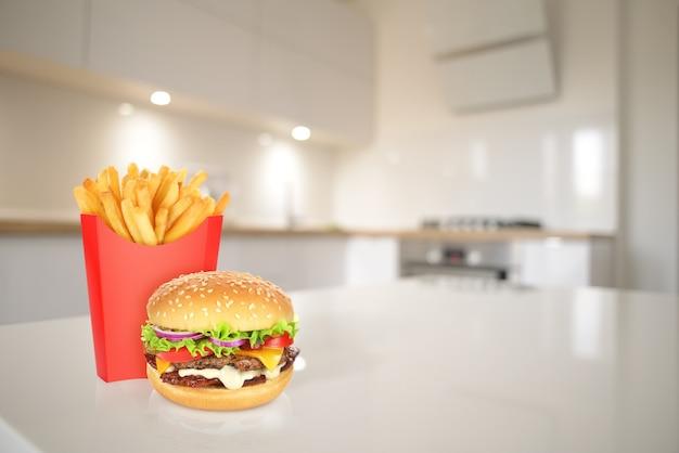 식탁에 있는 빨간 테이크아웃 상자에 치즈버거와 감자튀김. 선택적 초점