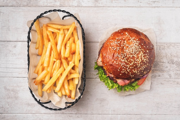 Cheeseburger and fries in a metal basket.