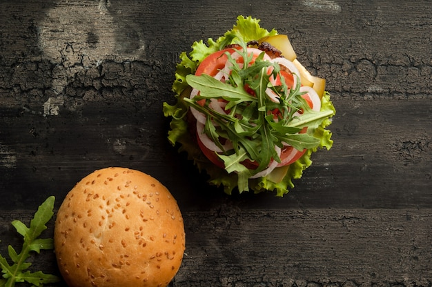 Cheeseburger on an old wooden surface of dark color hamburger with meat and tomato