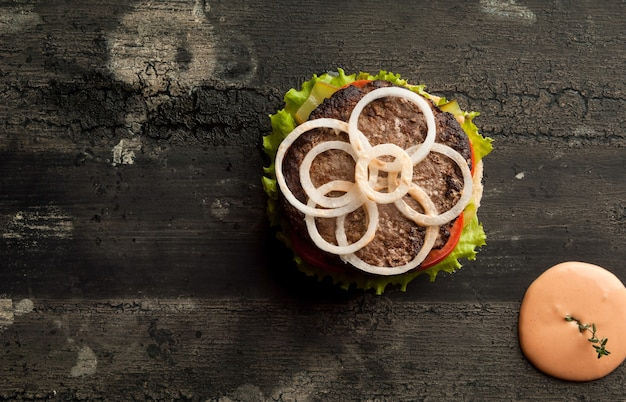 Cheeseburger on an old wooden surface of dark color hamburger with sauce and ketchup