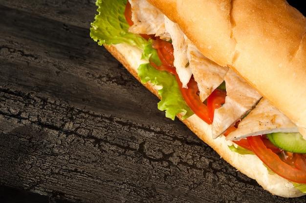 暗い色のハンバーガーの古い木製の表面にチーズバーガーと古い木製の鶏肉