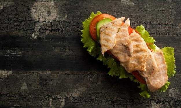 鶏肉と濃い色のハンバーガーの古い木製の表面にチーズバーガー