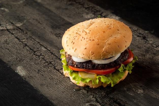肉とトマトの濃い色のハンバーガーの古い木製の表面にチーズバーガー