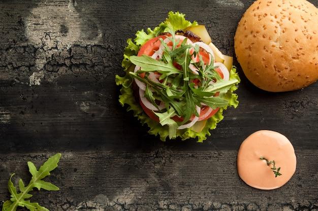 濃い色のハンバーガーの古い木の表面にソースとケチャップを添えたチーズバーガー