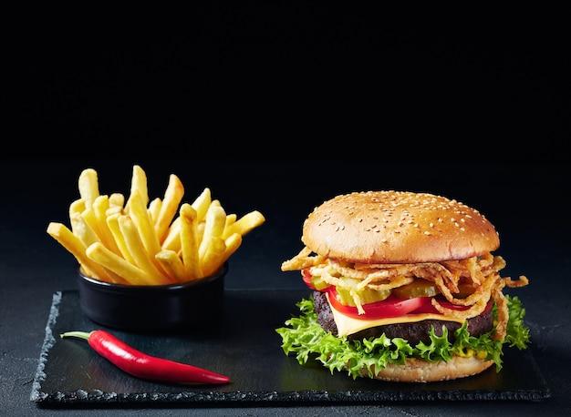Чизбургер с говяжьей котлетой, сыром чеддер, хрустящим жареным луком, салатом, нарезанными помидорами маринованные огурцы на черной каменной доске с картофелем фри на черной поверхности
