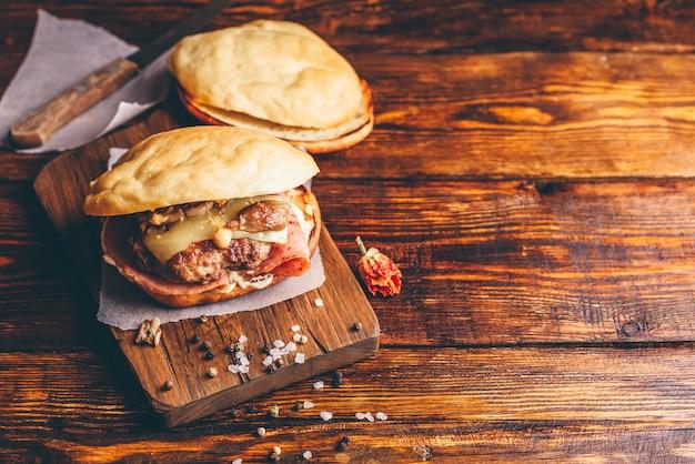 木製の背景とコピースペースにビーフパティとチーズバーガー。