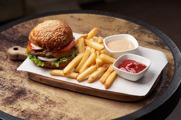 감자 튀김과 소스를 곁들인 치즈 버거. 나무 절단 보드에 신선한 햄버거와 감자 튀김. 패스트 푸드, 정크 푸드