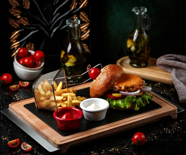 Cheeseburger with french fries on wooden board