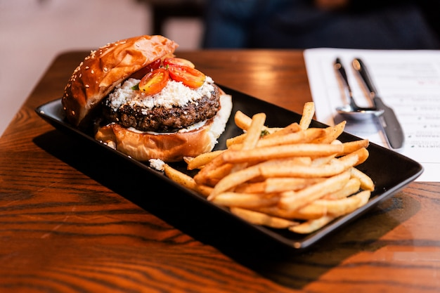 Cheeseburger with grilled beef, feta cheese and sliced tomato served with fries in black plate.