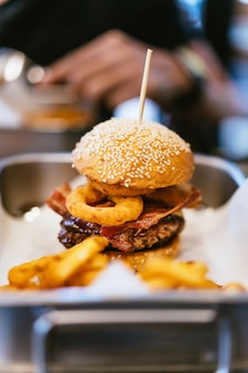 Cheeseburger with medium-rare grilled beef, crunchy bacon, onion rings