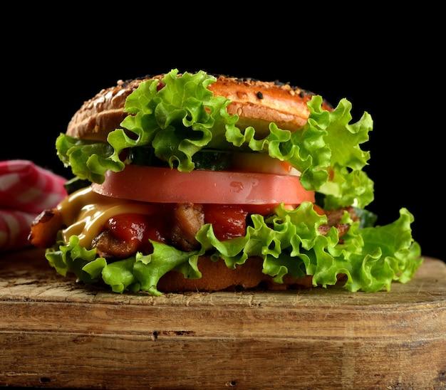 Чизбургер с фаршем, зеленым салатом и кетчупом на деревянной коричневой кухонной доске. черный фон