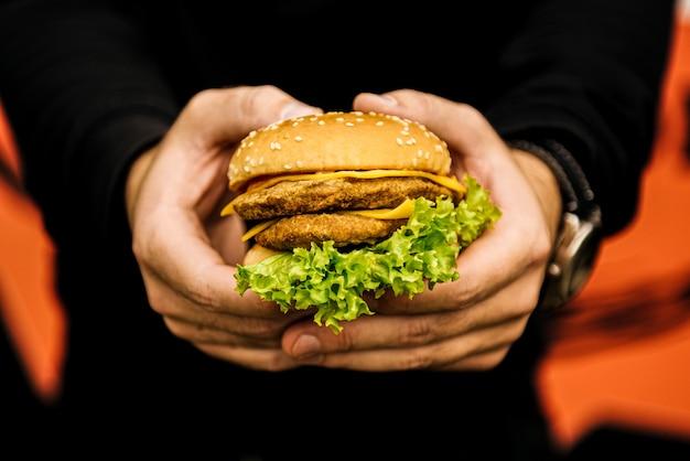 男性の手にチーズバーガー、ファーストフード