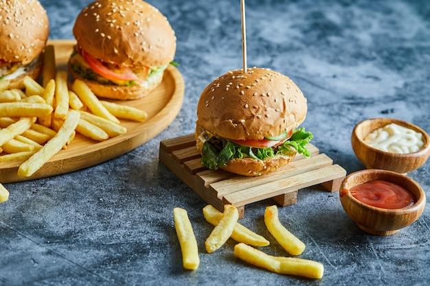 Cheeseburger con patate fritte sulla tavola di legno