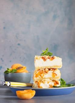 アプリコットとシュトロイゼルがミントで飾られたチーズケーキバー