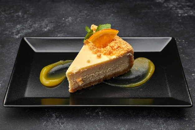 Cheesecake on a black plate, against a dark background