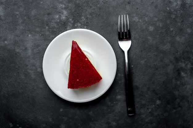 Cheesecake cake with raspberries on a white saucer on a stone background
