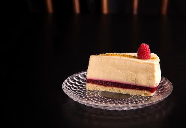 검은 배경에 라즈베리를 채운 치즈 케이크. 복사 공간