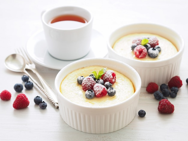 Cheesecake decorated with raspberries, blueberries and mint in two ramekin