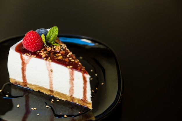 A cheesecake decorated with raspberry; blueberry and mint on plate against black background