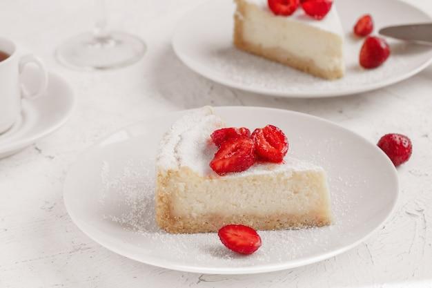 白い皿にイチゴで飾られたチーズケーキ