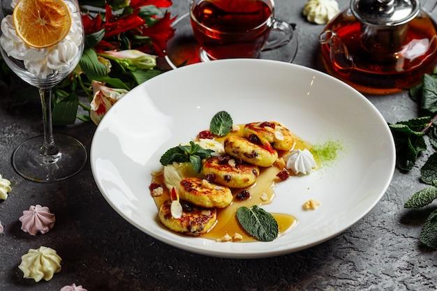 Чизкейк, свежее варенье и мята. творожные оладьи или творожные оладьи украшали сахарную пудру в тарелке крупным планом. здоровый и диетический завтрак.