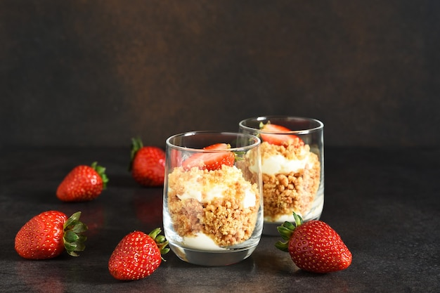 Cheesecake in a glass with strawberries on a dark concrete background. dessert in a glass.