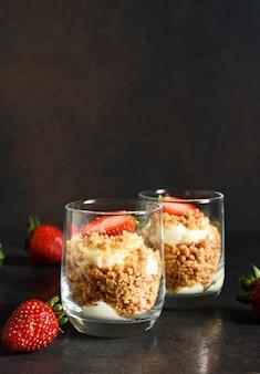 Чизкейк в стакане с клубникой на темном фоне бетона. десерт в стакане.